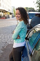 Confident woman with arms crossed standing next to car in urban setting