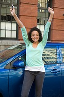 Excited woman with arms raised standing next to car in urban setting