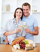 Smiling lovers drinking white wine in the kitchen
