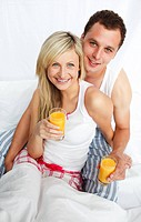 Young couple holding orange juice glasses in bed