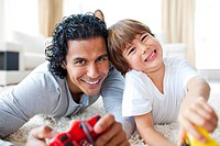 Animated little boy and his father playing video games lying on the floor