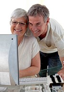 Smiling senior couple using a computer at home