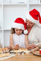 Grandmother and little girl baking Christmas cakes in the kitchen