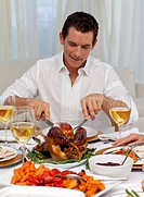 Attractive man eating turkey in Christmas dinner at home