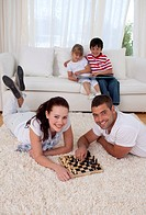 Couple playing chess on floor in living_room with their children on sofa