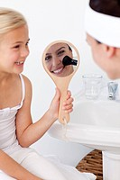Smiling daughter holding a mirror and mother putting makeup in bathroom