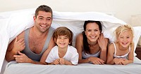 Happy parents and children playing in parent´s bed