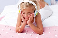 Little girl in bed with a headphones on listening to the music
