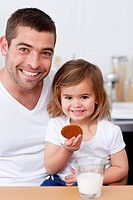 Father and daughter eating biscuits with milk in the kitchen