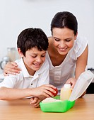 Mother and son making the school lunch in the kitchen