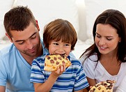 Happy boy eating pizza with ihs parents in living_room