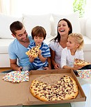 Happy parents and children eating pizza in living_room all together