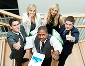 Young business team having a meeting on stairs with thumbs up
