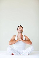 Young man sitting on bed doing yoga with copy_space