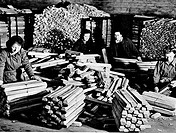 Four mid adult women bundling magnesium ingots
