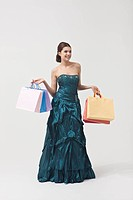 Portrait of beautiful woman wearing dress holding shopping bags