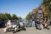 People, de Sluyswacht, Oude Schans, People sitting on bridge in the near of de Sluyswacht, a typical brown cafe at canal Oude Schans, Amsterdam, Holla...