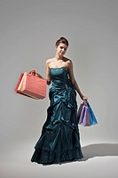 Young woman in long dress, holding shopping bags