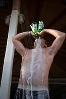 Man drinking four bottles of beer all at once during a beach party of the Super Paradise Club at Super Paradise Beach, knowing as a centrum of gays an...