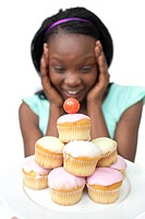Surprised young woman looking at cakes against a white background