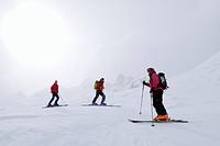 Skiers in diffus light, Cresta Bianca, Cristallo range, Dolomites, Veneto, Italy