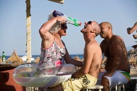 Man wearing crazy woman clothes shooting with a water pump gun in the mouth of an other man during a beach party at Super Paradise Beach, knowing as a...