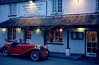 Two man driving an oldtimer in front of the Drunken Duck Inn, Lake District, Cumbria, England