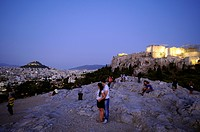 People at Areopag rock with view at the hill of Likavittos and Acropolis in the evening, Athens, Greece, Europe