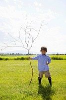 Young boy holding large stick in field