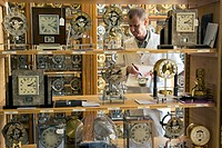Watchmaking. Worker surrounded by antique clocks in the antique repair workshop of the Jaeger_LeCoultre factory. Jaeger_LeCoultre JLC is one of the wo...