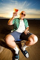 Bald guy on holidays sitting on a sunny beach holding a cocktail