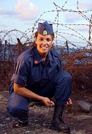 Military girl tying her boots with a spike fence in background