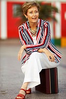 White, blue and red stripes dressed mature woman sitting