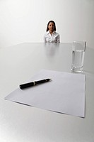 Young woman sits at end of the table waiting to be interviewed