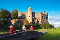 Wales, Carmarthenshire, Laugharne, Visitors crossing a footbridge by Laugharne Castle, a thirteenth century castle converted to a Tudor mansion in the...