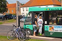 Passengers boarding a bus in The Popular North Norfolk village of Burnham Market in Norfolk Uk