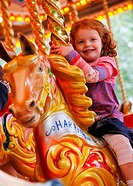 England, West Midlands, Birmingham, A young girl enjoying a ride on a fairground carousel horse.