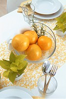 Table with plates and bowl of oranges