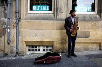 Scotland, City of Edinburgh, Edinburgh, A saxophonist busking on a street near The Royal Mile in Edinburgh
