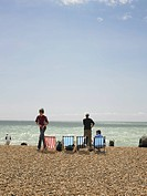England, East Sussex, Brighton, Deckchairs and people on Brighton beach on a sunny day with blue sky.