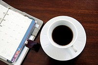 Cup of coffee next to a diary
