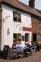 England, Staffordshire, Lichfield, People sitting at outdoor tables in Dam Street outside cafe in the historic city centre.