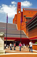 England, London, Somers Town, People leaving and arriving through the piazza of the British Library past one of eight Anthony Gormley granite boulders...