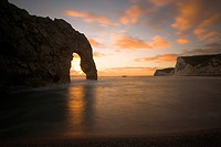 England, Dorset, Durdle Door, Sunset at Durdle Door, a natural limestone arch on the Jurassic Coast in Dorset