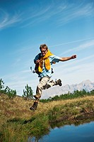 Austria, Salzburger Land, Man jumping by waterside, laughing, portrait