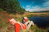 Austria, Salzburger Land, Woman relaxing near lake