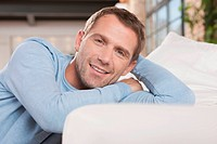 Germany, Cologne, Man sitting by sofa, smiling, portrait
