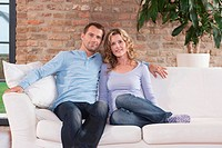 Germany, Cologne, Couple sitting on sofa, smiling, portrait