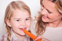 Germany, Cologne, Mother and daughter 4_5 daughter eating a carrot, portrait, close_up