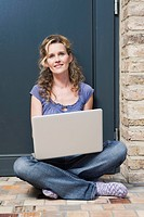 Germany, Cologne, Woman sitting in front of door using laptop, smiling, portrait